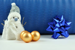 Snowman and Christmas Balls. Snowman, blue ribbon, and golden Christmas balls with a blue background Stock Image