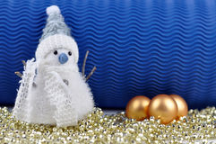 Snowman and Christmas Balls. Snowman with garland and golden Christmas balls with a blue background Stock Image
