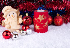 Snowman with christmas balls on snow. Candle, christmas balls and snowman on snow Royalty Free Stock Photo