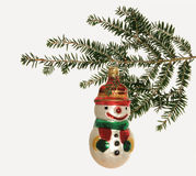Snowman Christmas Decotation. Snowman Christmas decoration hanging on a pine bough set against a white background Stock Images
