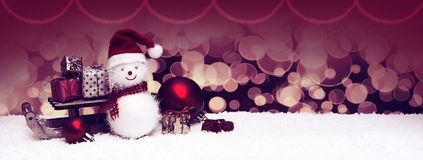 Snowman with Christmas gifts on the sledge isolated on blur background. Christmas snowman with red scarf and santa claus hat , isolated on blur background Stock Photos