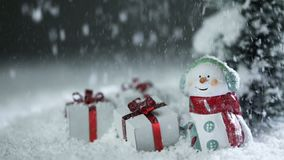 Snowman and christmas gifts under snow