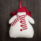 Snowman Christmas handmade toy. Hand made felt  snowman Christmas decoration. Christmas toy. Vintage style, over wood background Stock Image