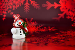 Snowman Christmas. Little Snowman figurine in front of a red Christmas background Stock Photo
