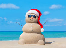 Snowman in Christmas Santa hat and sunglasses at ocean beach Stock Photo
