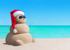 Snowman in Christmas Santa hat and sunglasses at sea beach. Happy sandy snowman in Christmas Santa Claus hat and sunglasses at sunny sea beach, New Year holiday Stock Images