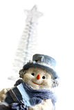 Snowman and Christmas Tree. Shot of Snowman figurine with a christmas tree in the background Stock Photography