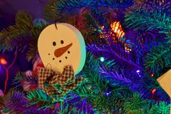 Snowman christmas tree decoration with bow tie. Snowman Christmas Decoration on a christmas treee brightly lit with colored light Stock Image