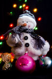 Snowman and Christmas tree decorations. Snowman on the background of colored lights and garlands of Christmas tree decorations Royalty Free Stock Photos