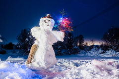 Snowman With A Christmas Tree. A snowman holding a lit branch of a pine tree on a yard on a dark night stock photo