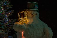 Snowman beside a Christmas tree at night. stock photos