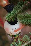 Snowman Christmas Tree Ornament. Snowman ornament hanging on an evergreen Christmas tree with a carrot nose and a black top hat Royalty Free Stock Photos