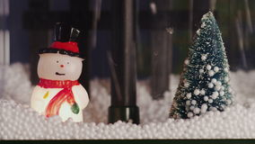 Snowman and Christmas tree. Which is filled with artificial snow stock video footage