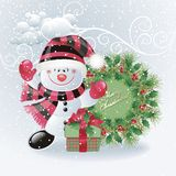 Snowman with christmas wreath Royalty Free Stock Image