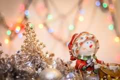 Snowman close-up on the background of blurry colored lights tinsel and Happy New Year royalty free stock photography