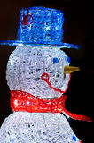 Snowman closeup profile with blue hat and red scarf on black background Royalty Free Stock Photos
