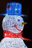 Snowman closeup profile with blue hat and red scarf on black background Stock Photo