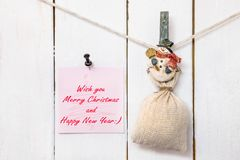 Snowman clothespin holding sack and Christmas greeting note Royalty Free Stock Photo