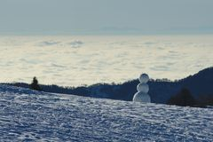 Snowman with clouds and haze in background. Snowman made of three snowballs with clouds and haze in background Royalty Free Stock Photos