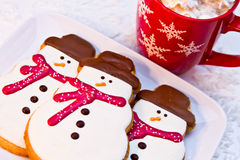 Snowman Cookies. Close up of 3 snowmen cookies with red scarves sitting on a white plate with red snowflake mug filled with hot cocoa Royalty Free Stock Images