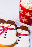 Snowman Cookies. Snowmen sugar cookies with red scarves sitting on white plate with a red mug filled with hot chocolate and whipped cream Stock Photography