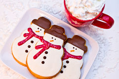 Snowman Cookies. 3 snowmen sugar cookies with red scarved sitting on a white plate with a red mug filled with hot chocolate Stock Photos