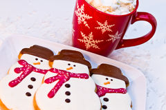 Snowman Cookies. Plate of snowmen sugar cookies for Santa with red snowflake mug filled with hot chocolate and whipped cream Stock Images