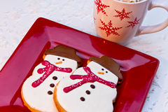 Snowman Cookies. 2 snow man sugar cookies with red scarves sitting on red plate and white snowflake mug filled with hot cocoa Royalty Free Stock Photo