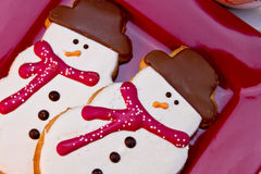 Snowman Cookies. Close up 2 snowmen sugar cookies with red scarves sitting on red plate Royalty Free Stock Photography