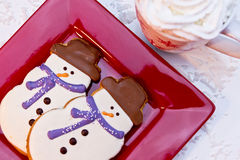 Snowman Cookies. Snowmen holiday cookies with blue scarves sitting on red plate with mug of hot chocolate and whipped cream Royalty Free Stock Image