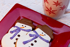 Snowman Cookies. Holiday snowmen sugar cookies sitting on a red plate with cup of hot chocolate Stock Photo