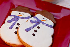 Snowman Cookies. Close up of 2 snowmen sugar cookies with blue scarves sitting on red plate Royalty Free Stock Images