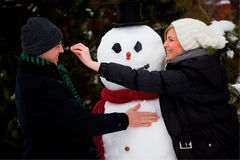 Snowman couple. Lovely couple building snowman in wintertime Stock Photo