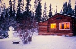 Snowman cozy illuminated log cabin winter vacation Royalty Free Stock Image