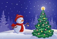 Snowman decorating a tree Royalty Free Stock Photos