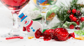 Snowman decoration, wine and sweets on a Christmas table. Stock Photography