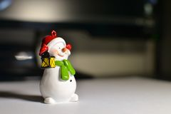 Snowman on the desktop in front of the computer.  Royalty Free Stock Images