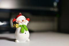 Snowman on the desktop in front of the computer.  Royalty Free Stock Image
