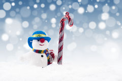 Snowman doll with candy cane Royalty Free Stock Photos
