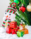 Snowman. Doll with gift box decorated Christmas tree Stock Photos