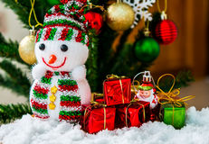 Snowman. Doll with gift box decorated Christmas tree Royalty Free Stock Image