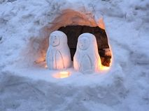Snowman doll lovers in an ice cave with candle lights royalty free stock images