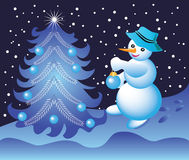 Snowman dresses up Christmas tree Stock Images