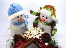 Snowman duo with a snow star. And two tassels on white background Royalty Free Stock Image