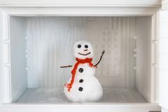 Snowman in empty freezer. Buildup of ice, cleaning and servicing concept. Funny diet idea stock photo