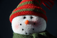 Snowman Face. Closeup of lit up knitted snowman's face with dark background Royalty Free Stock Photos