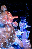 Snowman family. Three decorative lighted snowman stands in the park with holiday Christmas lights royalty free stock photos