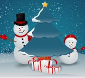 Snowman family in Christmas winter scene with gift box Stock Photos
