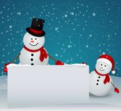 Snowman family in Christmas winter scene with sign Royalty Free Stock Photography