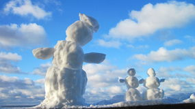 Snowman family. In cloudy sky background, Lithuania Stock Image